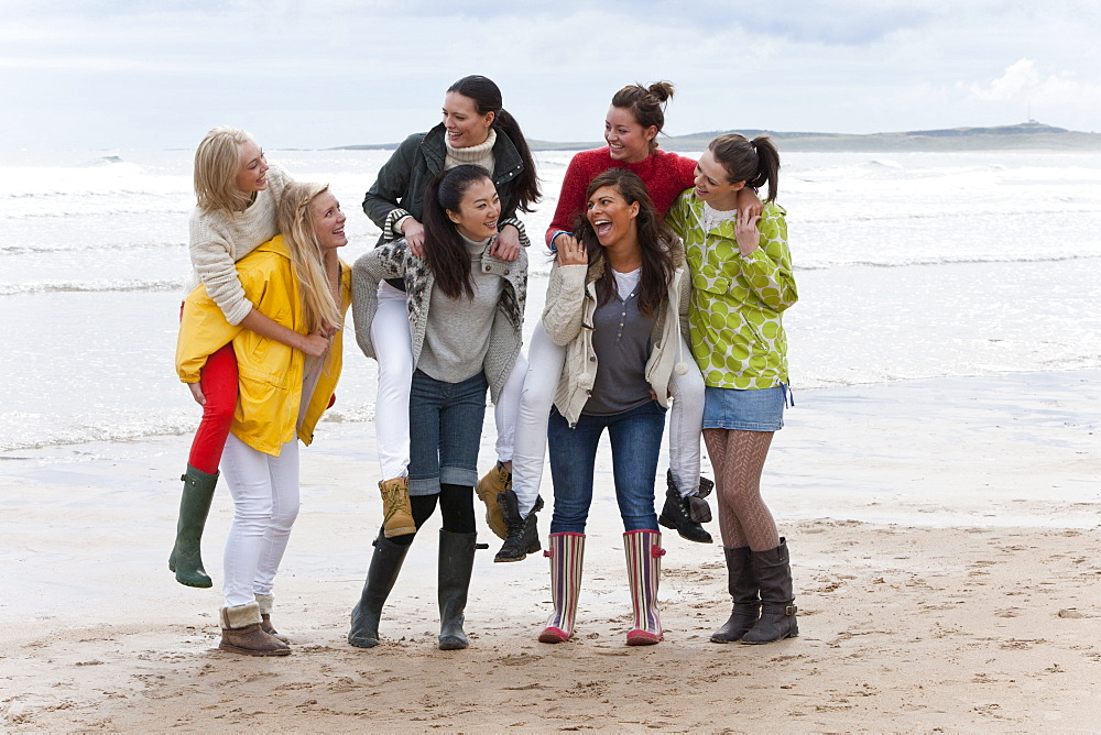 Smiling young women piggybacking on beach