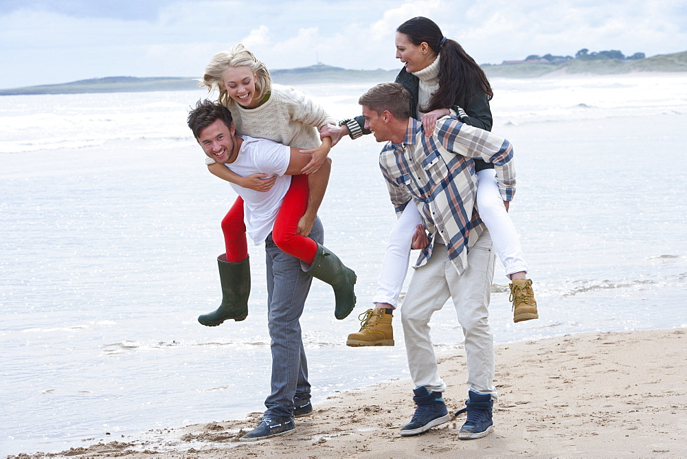 Young couples piggybacking on beach