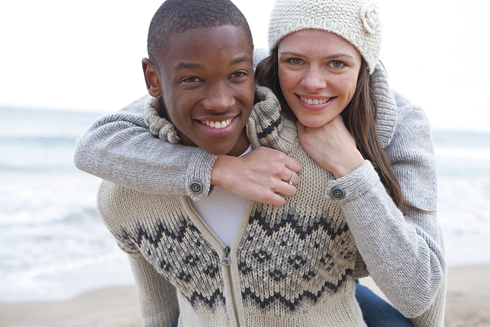 Portrait of smiling young couple piggybacking on beach