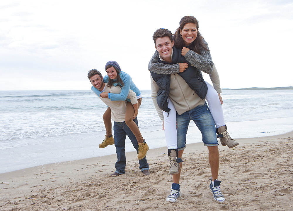Portrait of smiling young couples piggybacking on beach
