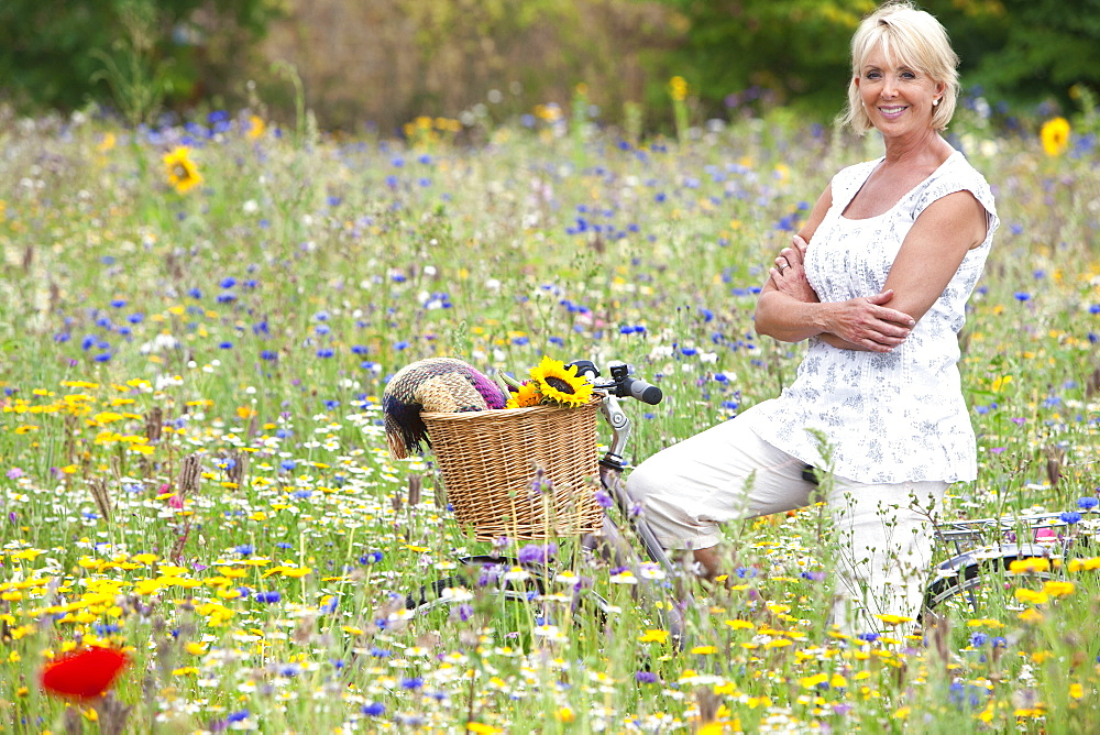 Smiling woman sitting on bicycle in field of wildflowers - 786-7794