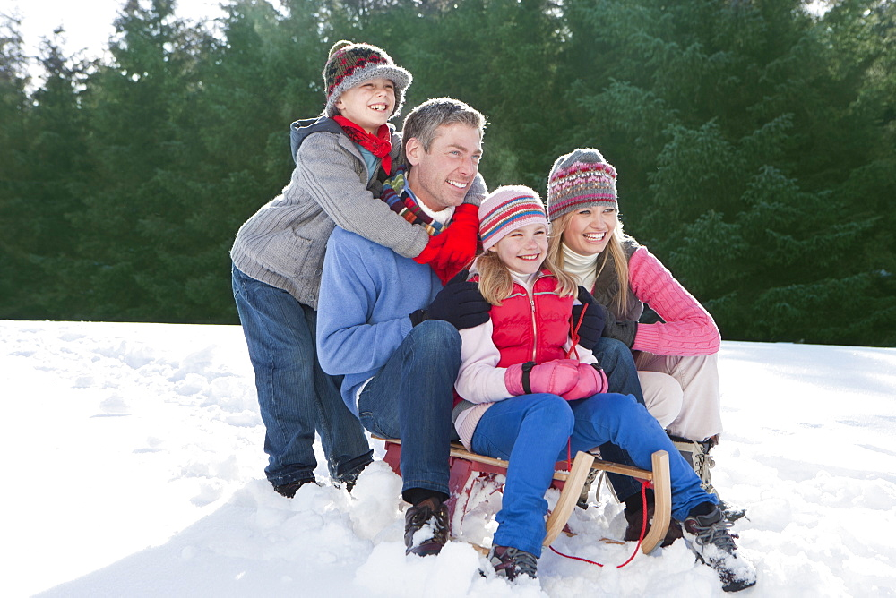 Happy family sitting on sled in snow