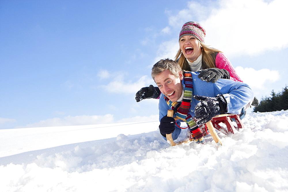 Happy couple sledding down snowy hill