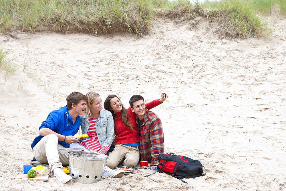 Teenage couples barbecuing and taking self-portrait on beach