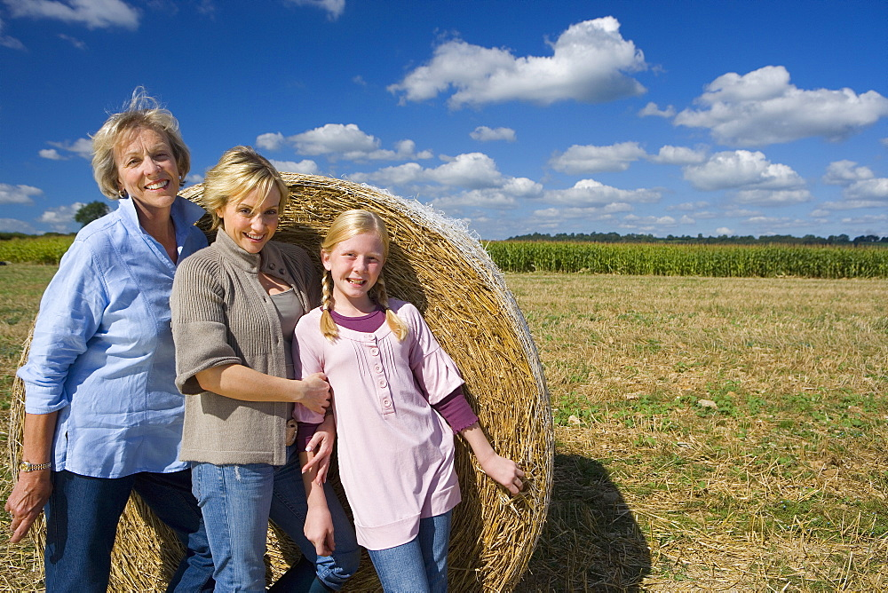 Family of three generations of women by bale of hay in field, smiling, portrait