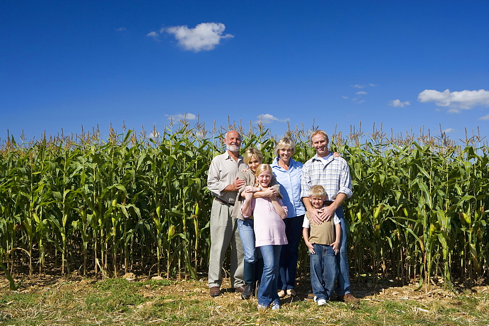 Family of three generations arm in arm by cornfield, smiling, portrait