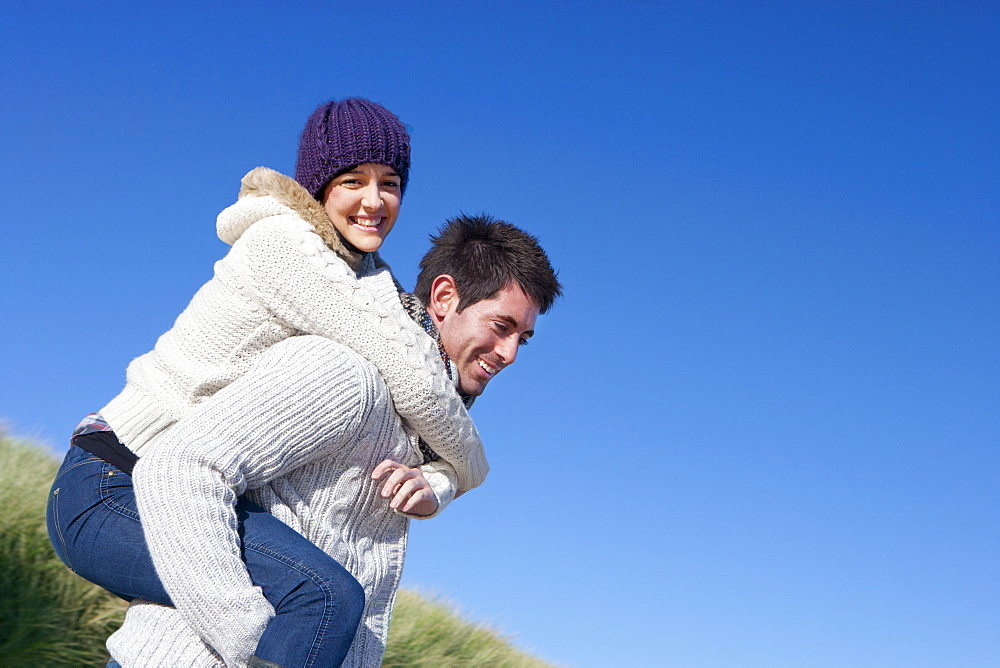 Man piggybacking woman against sunny, blue sky