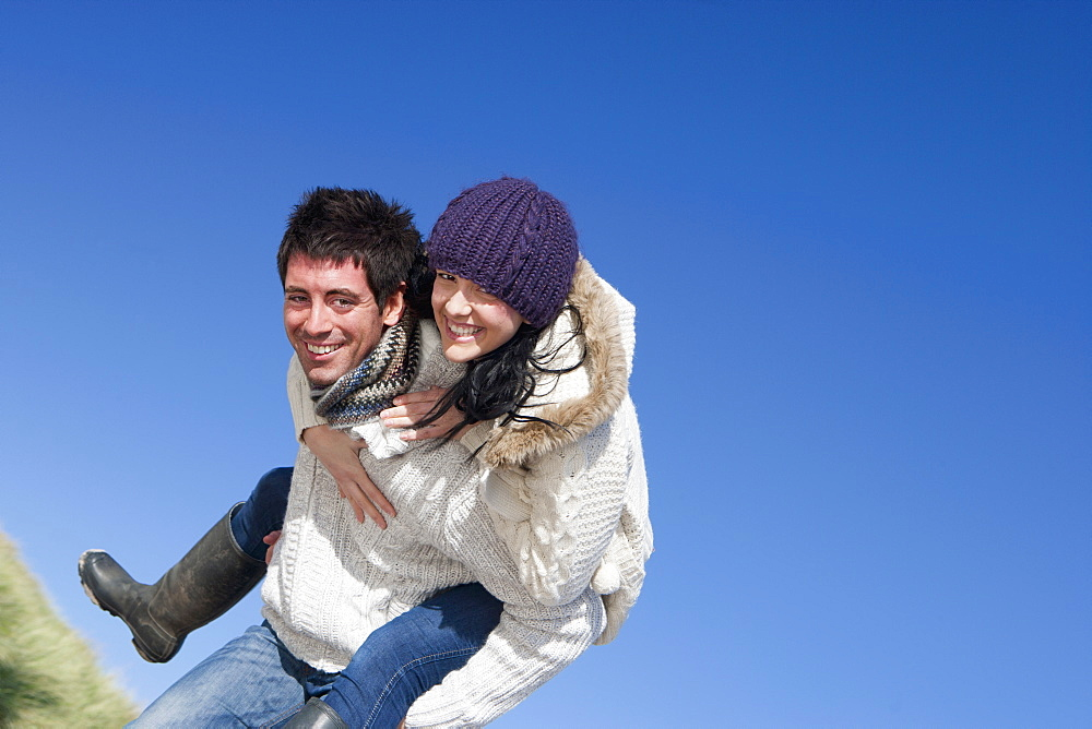 Portrait of man piggybacking woman against sunny, blue sky
