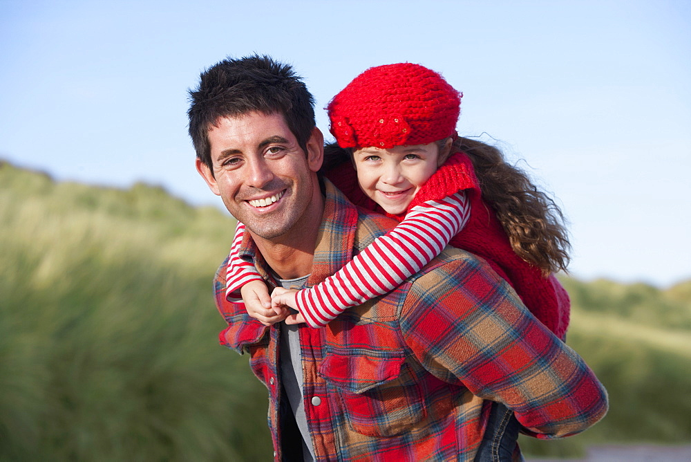 Portrait of smiling father piggybacking daughter