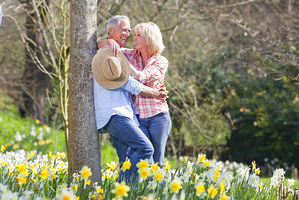 Smiling senior couple hugging and leaning on tree trunk in sunny daffodil field