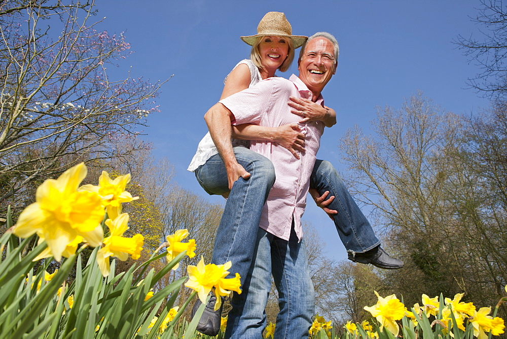 Portrait of happy senior couple piggybacking in sunny daffodil field