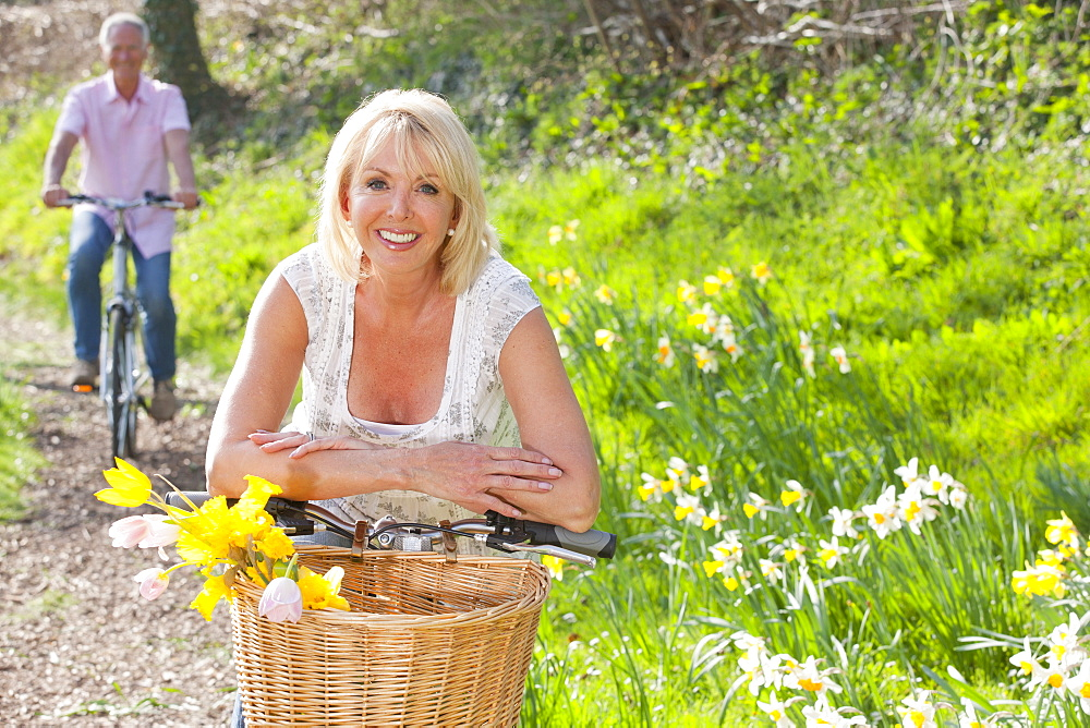 Portrait of smiling woman leaning on bicycle with spring flowers in basket - 786-8068