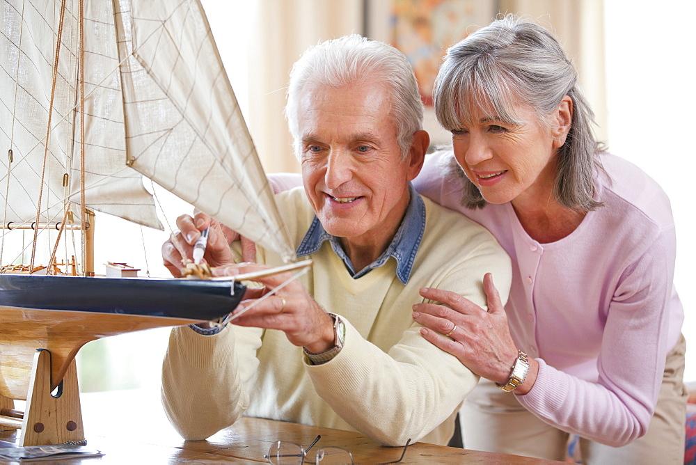 Senior woman watching senior man apply glue to model sailboat
