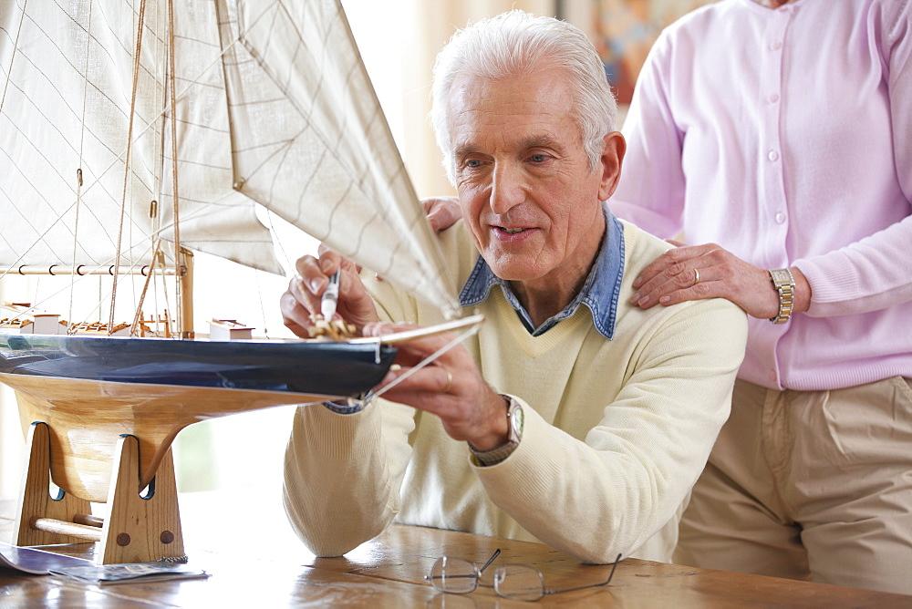 Senior woman standing behind senior man applying glue to model sailboat
