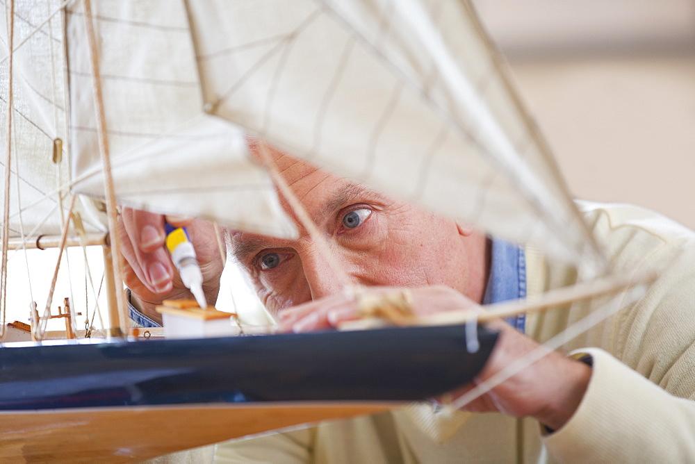 Close up of senior man applying glue to model sailboat