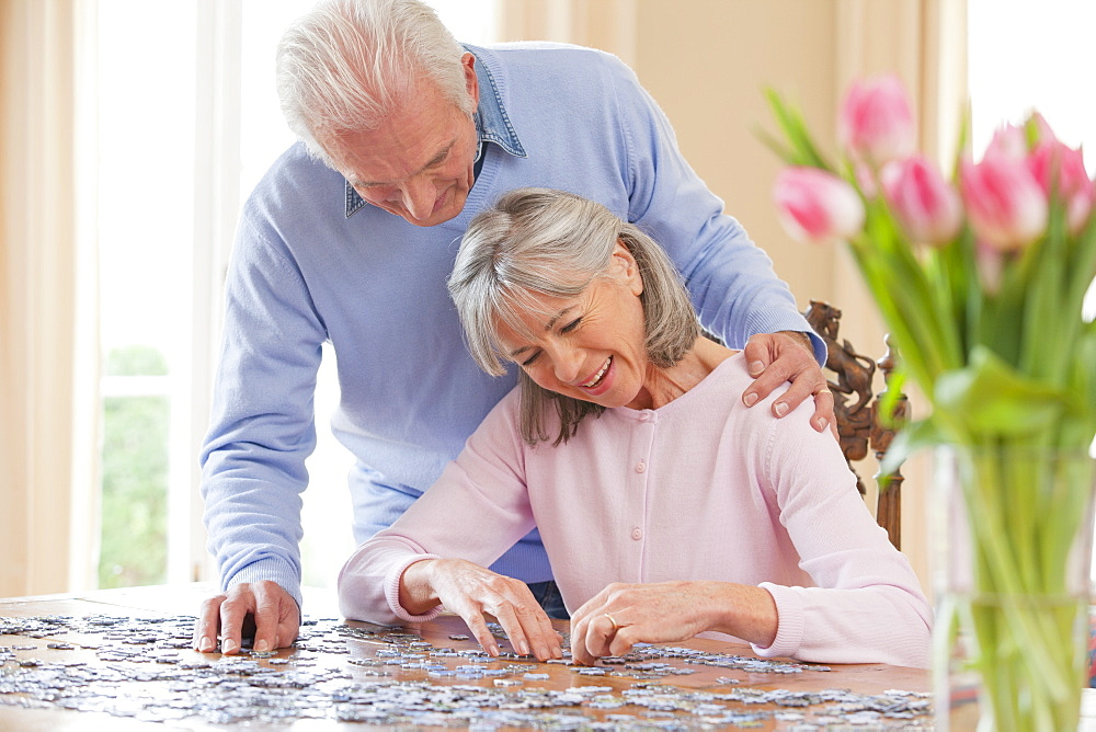 Smiling senior couple assembling jigsaw puzzle on table