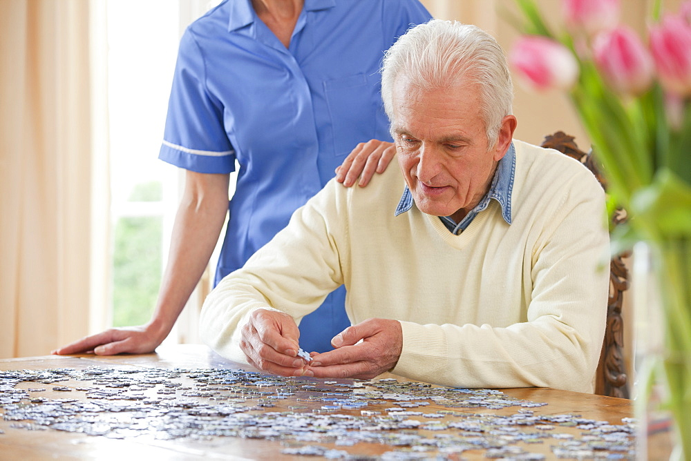 Home caregiver standing behind senior man assembling jigsaw puzzle on table