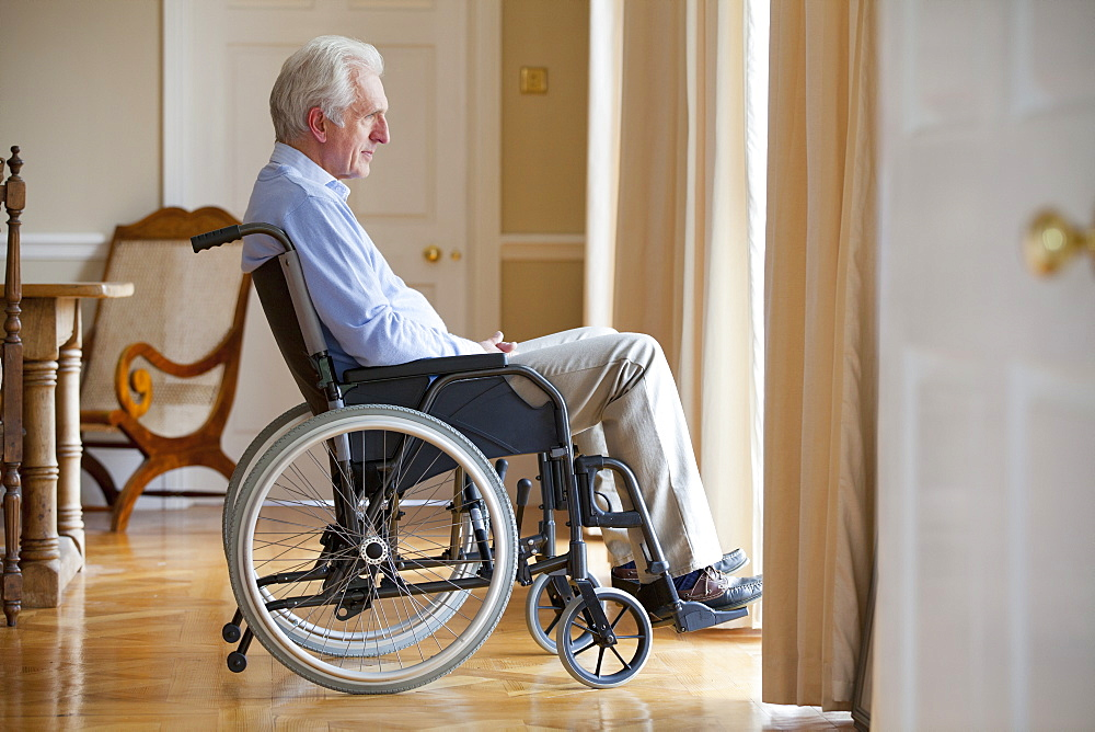 Senior man sitting in wheelchair and looking out window