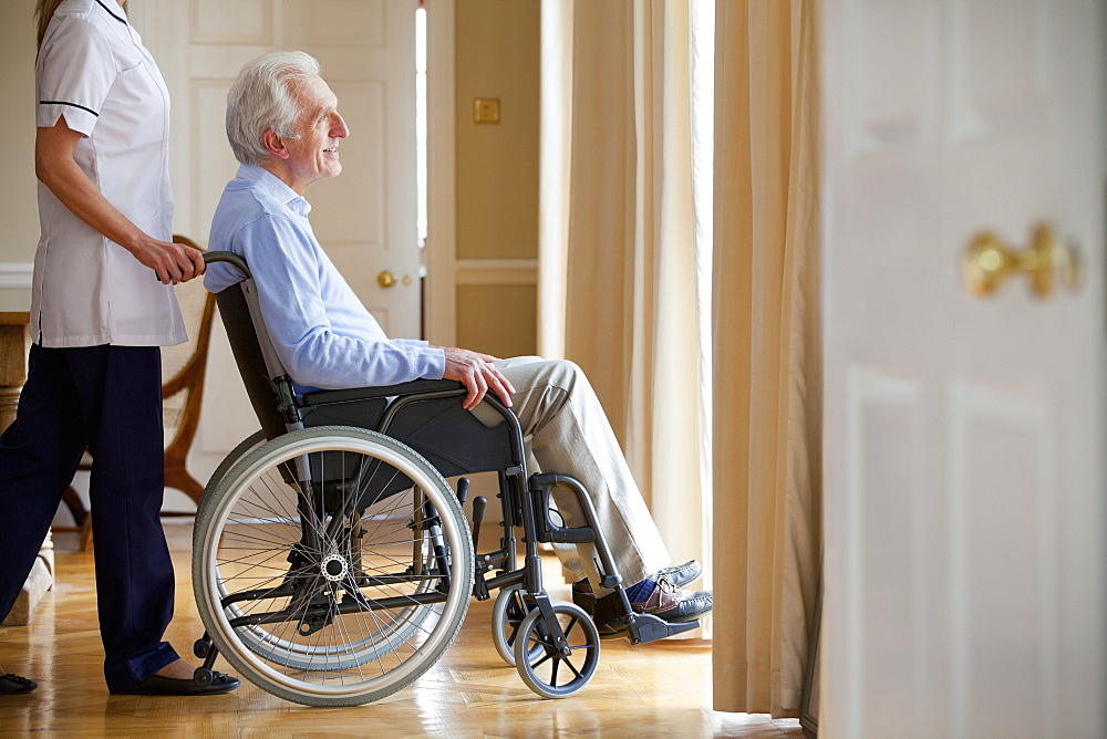 Home caregiver pushing senior man in wheelchair to window