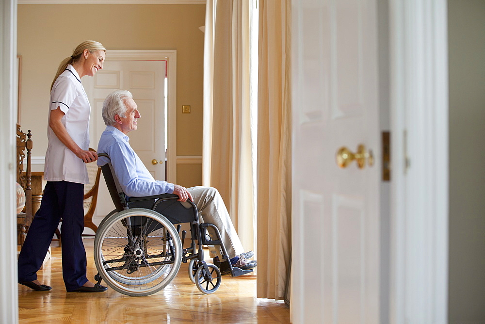 Smiling home caregiver pushing senior man in wheelchair to window