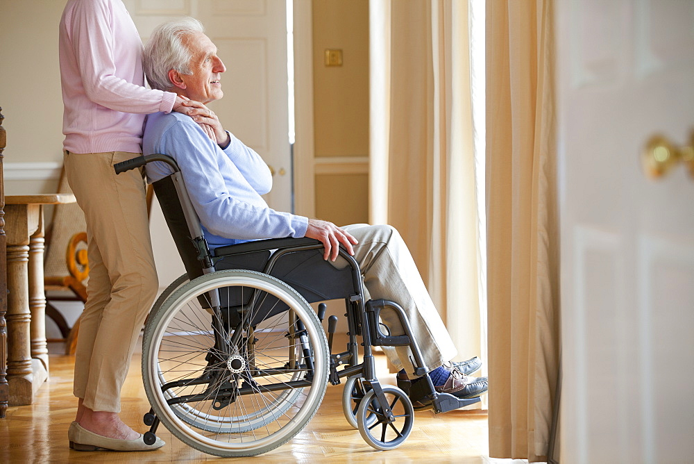 Senior woman holding hands with senior man in wheelchair at window