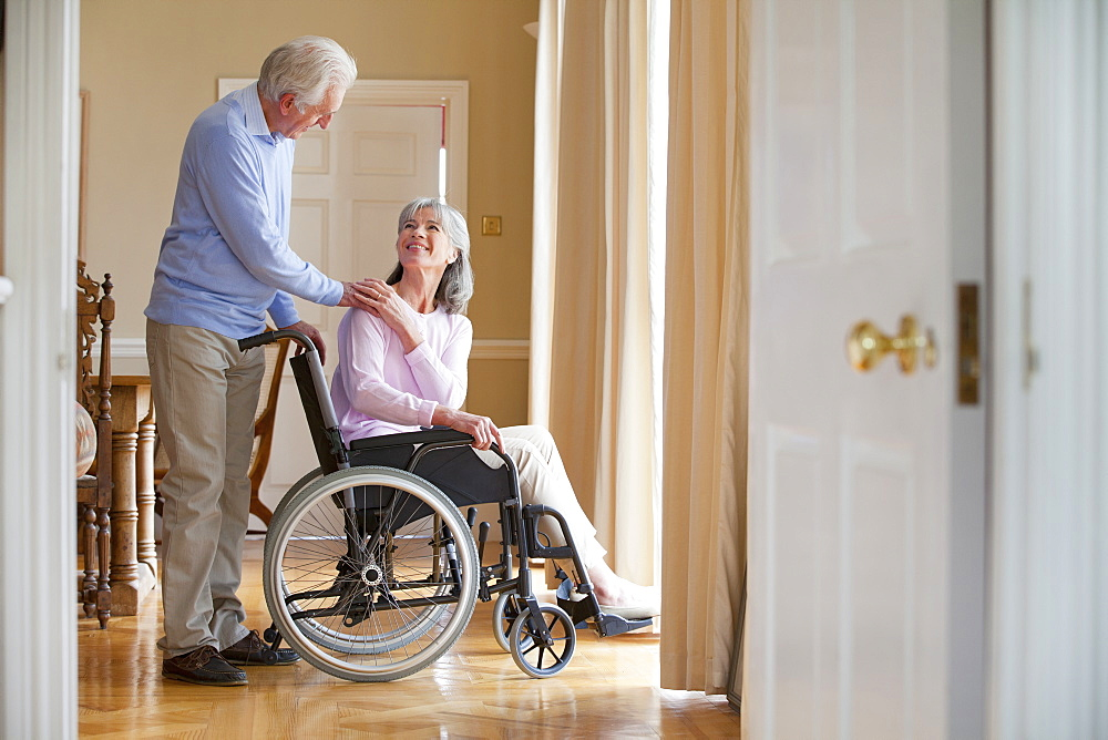 Senior man holding hands with senior woman in wheelchair at window