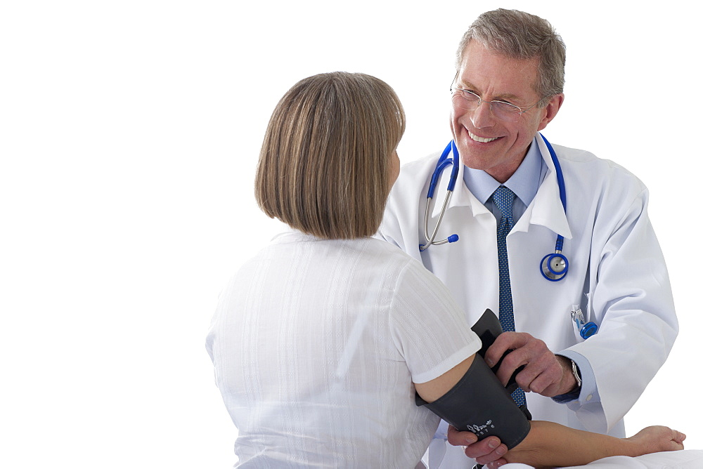 Cut Out Of Senior Male Doctor Taking Patient's Blood Pressure