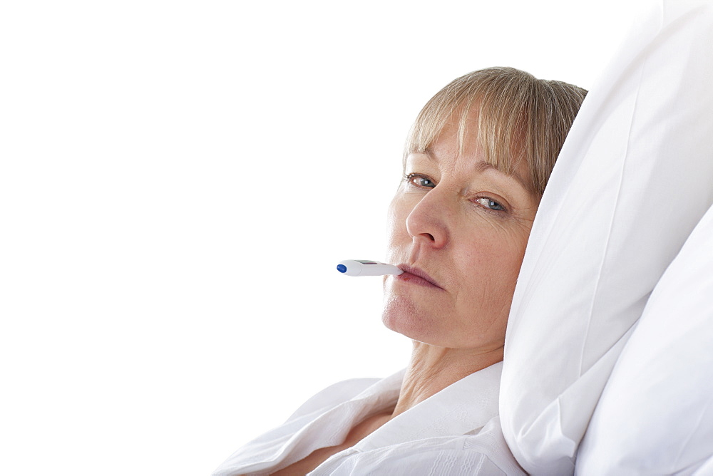 Cut Out Of Middle Aged Female Patient Having Temperature Taken
