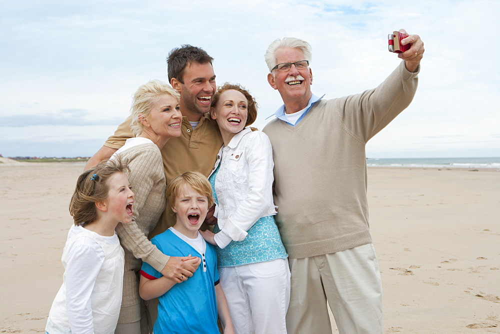 Taking Photo Of Multi Generation Family On Beach Holiday