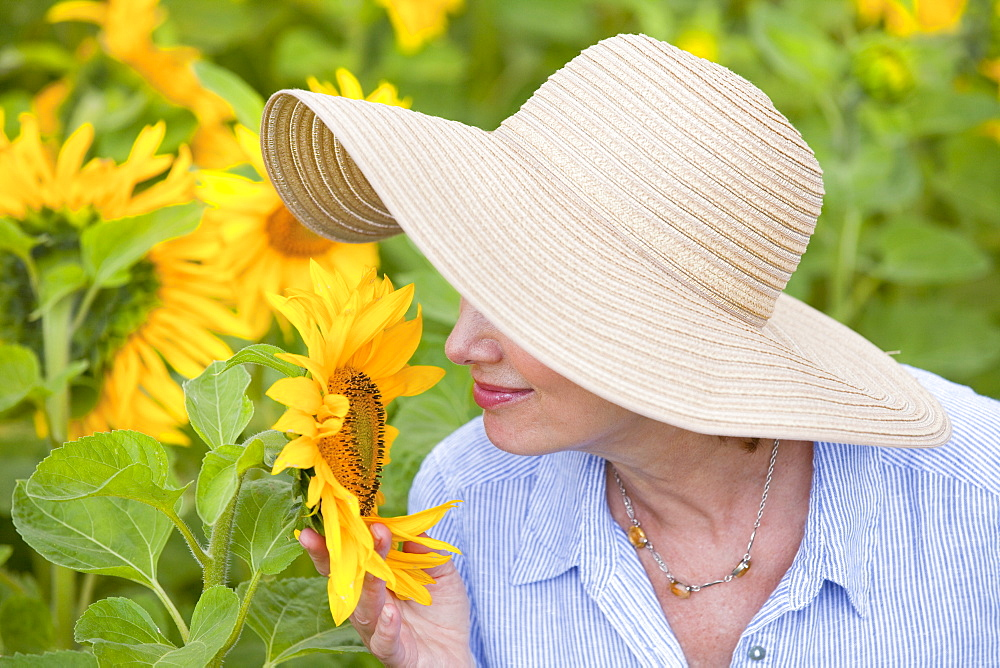 Close up of woman in sun hat smelling sunflower