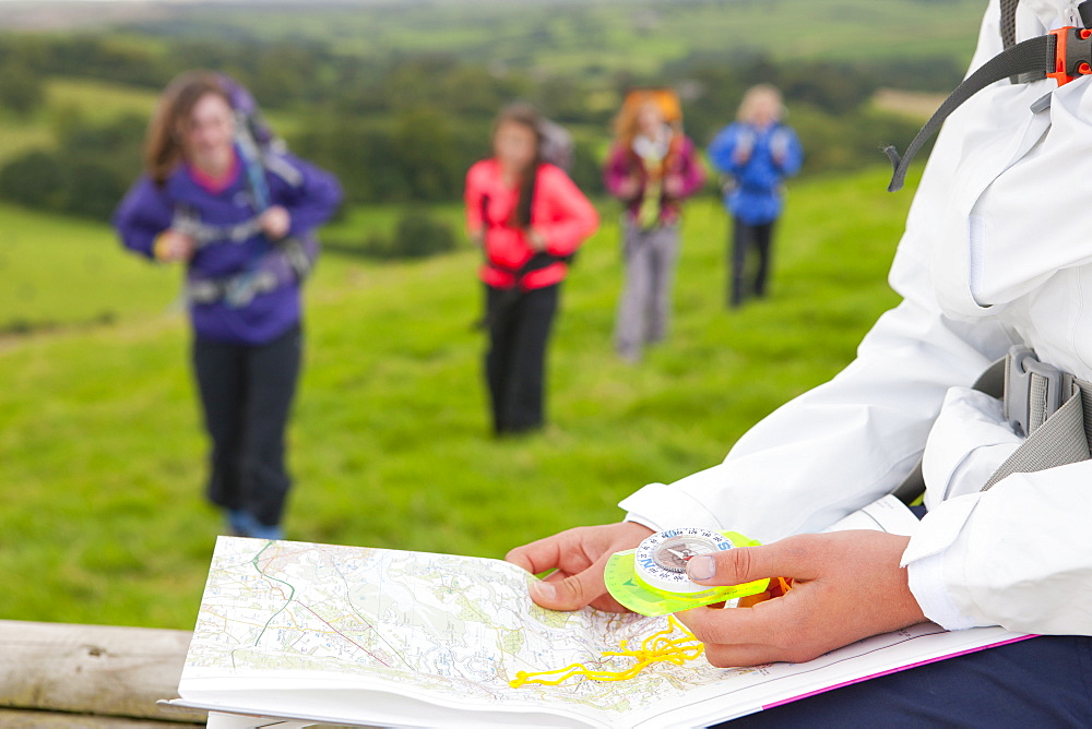 Close up of girl holding compass and map in field
