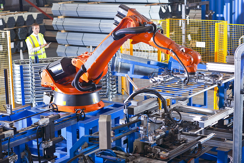 Worker controlling robotic machinery lifting steel fencing on production line in manufacturing plant - 786-8845