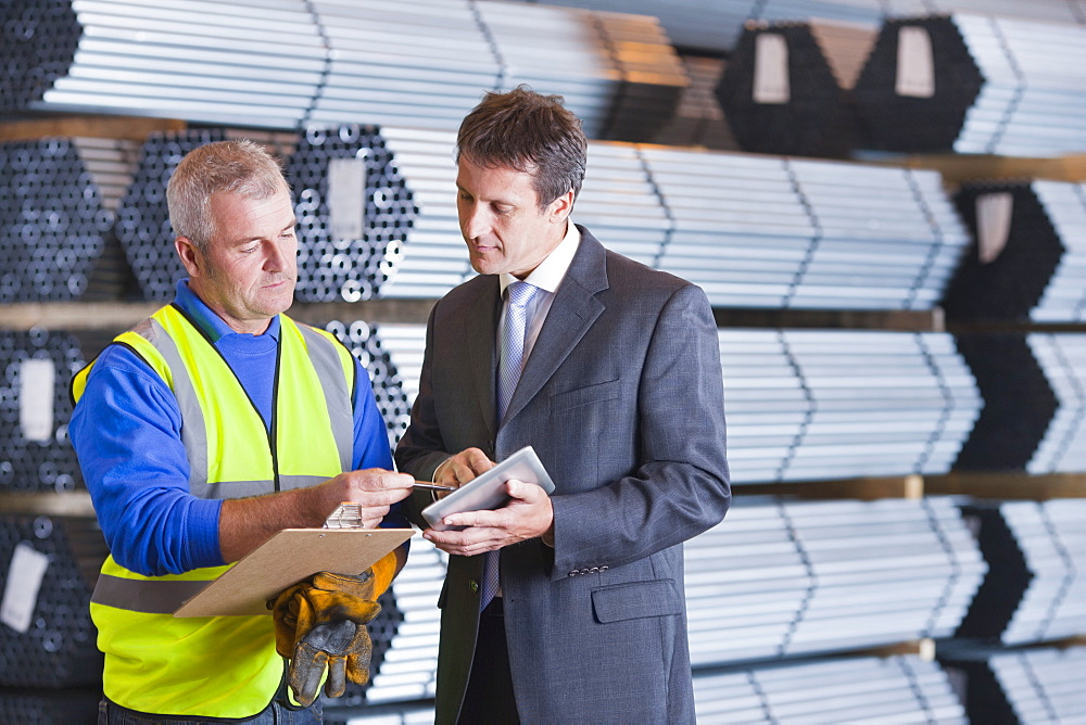 Businessman and worker with clipboard and digital tablet in front of steel tubing - 786-8859