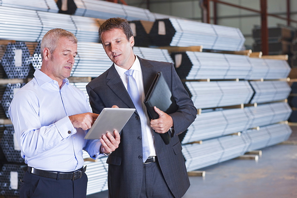 Bank manager and business owner using digital tablet in front of steel tubing in warehouse