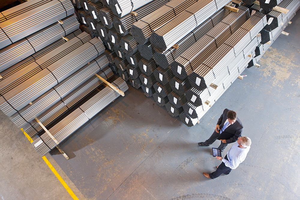 Bank manager and businessman using digital tablet near steel tubing in warehouse