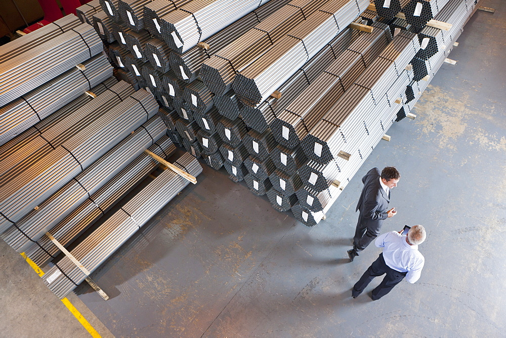 Bank manager and businessman talking near steel tubing in warehouse