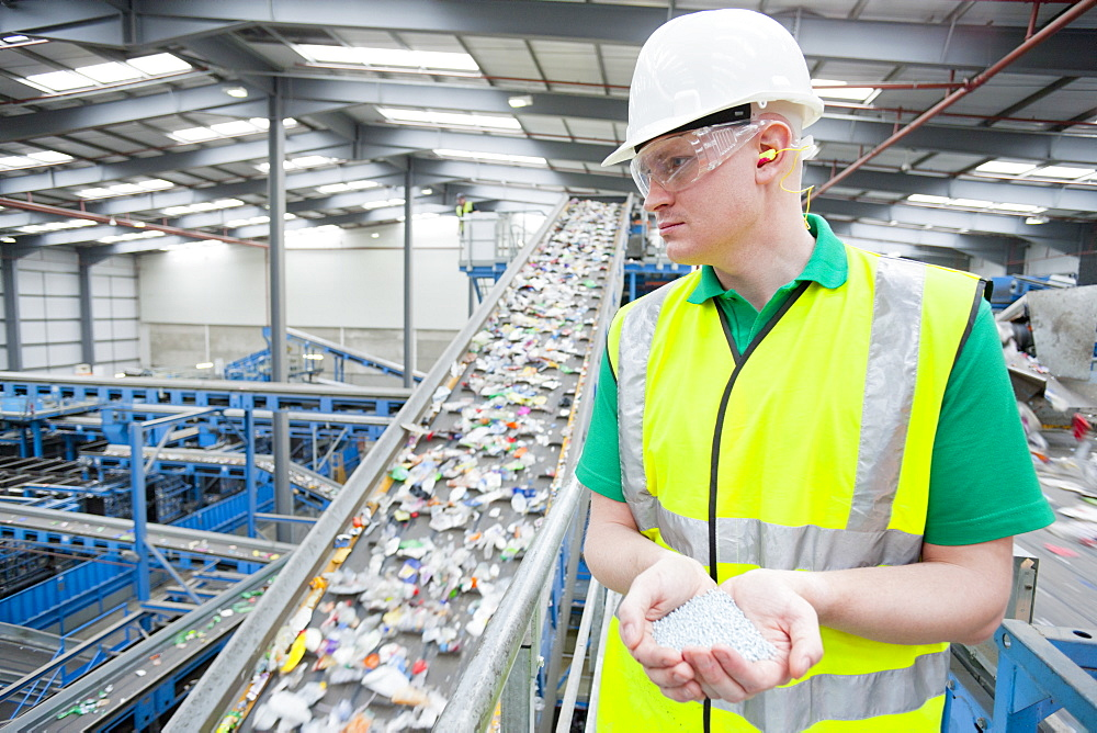 Worker holding plastic pellets near conveyor belt in recycling plant