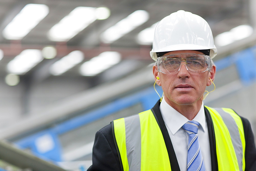 Close up portrait of serious businessman wearing hard-hat, goggles and reflector-vest in recycling plant