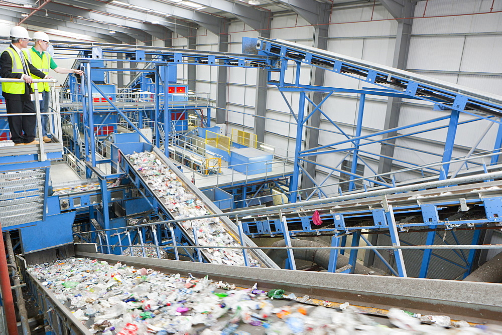 Businessman and worker on platform above conveyor belts in recycling plant
