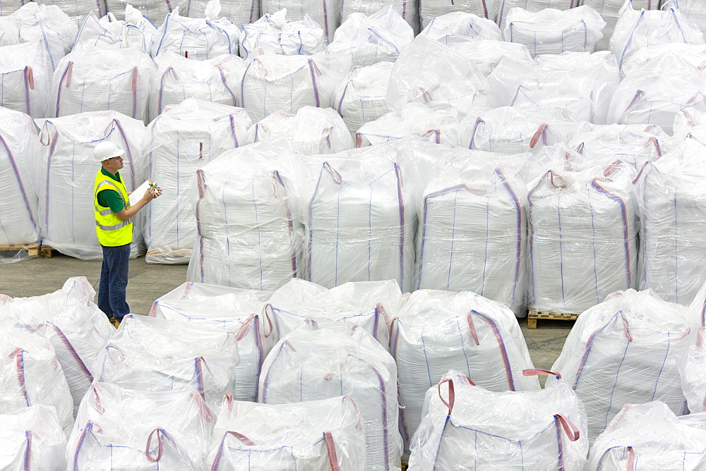 Worker with clipboard among large bags of plastic pellets in warehouse