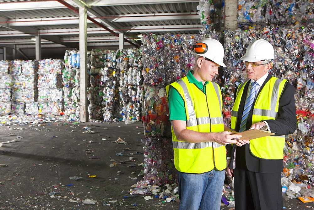 Businessman and worker with clipboard in recycling plant