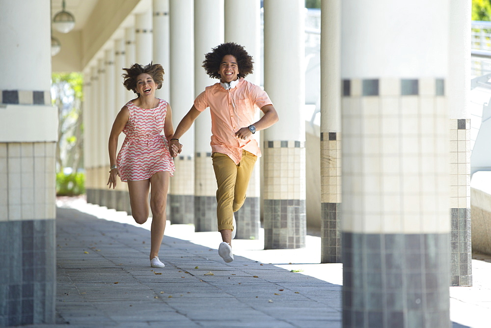 Smiling young couple holding hands and running along corridor