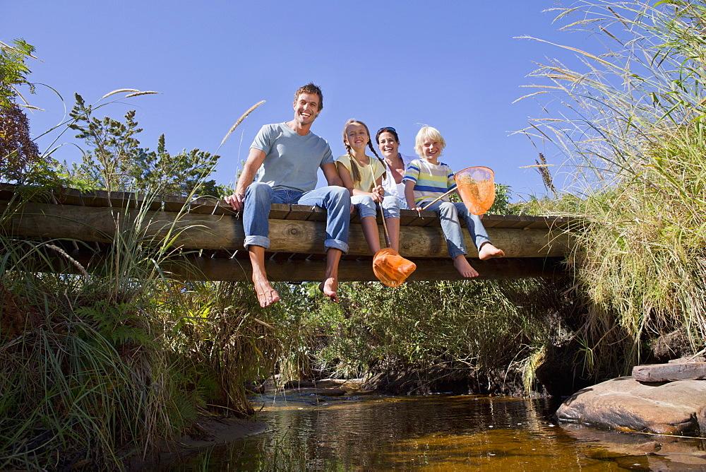 Portrait of smiling family sitting on footbridge over stream