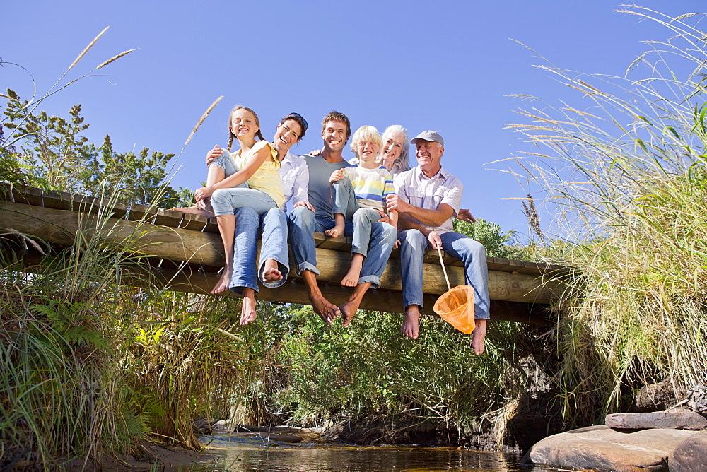 Portrait of smiling multi-generation family sitting barefoot on footbridge over stream