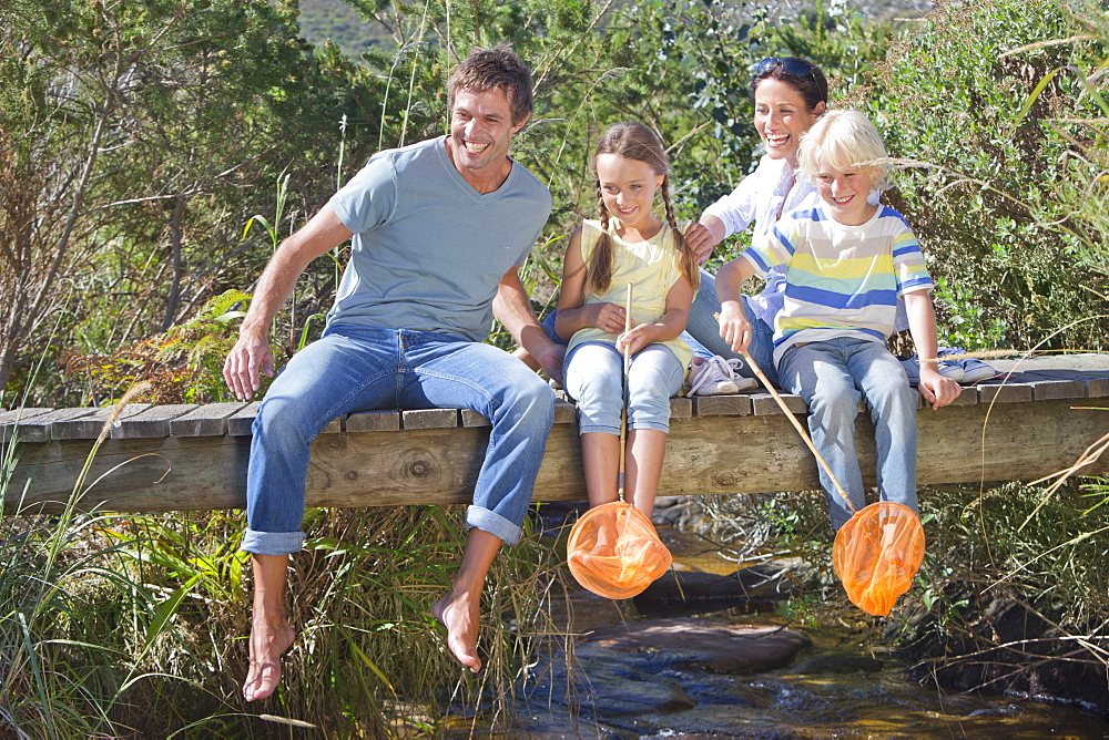 Happy family with fishing nets sitting on footbridge over stream