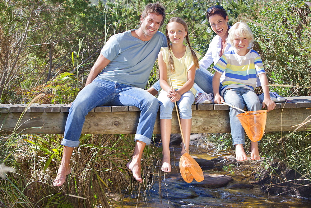 Portrait of smiling family with fishing nets sitting barefoot on footbridge over stream