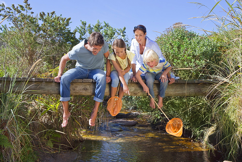 Family with fishing nets sitting barefoot on footbridge and looking down at stream