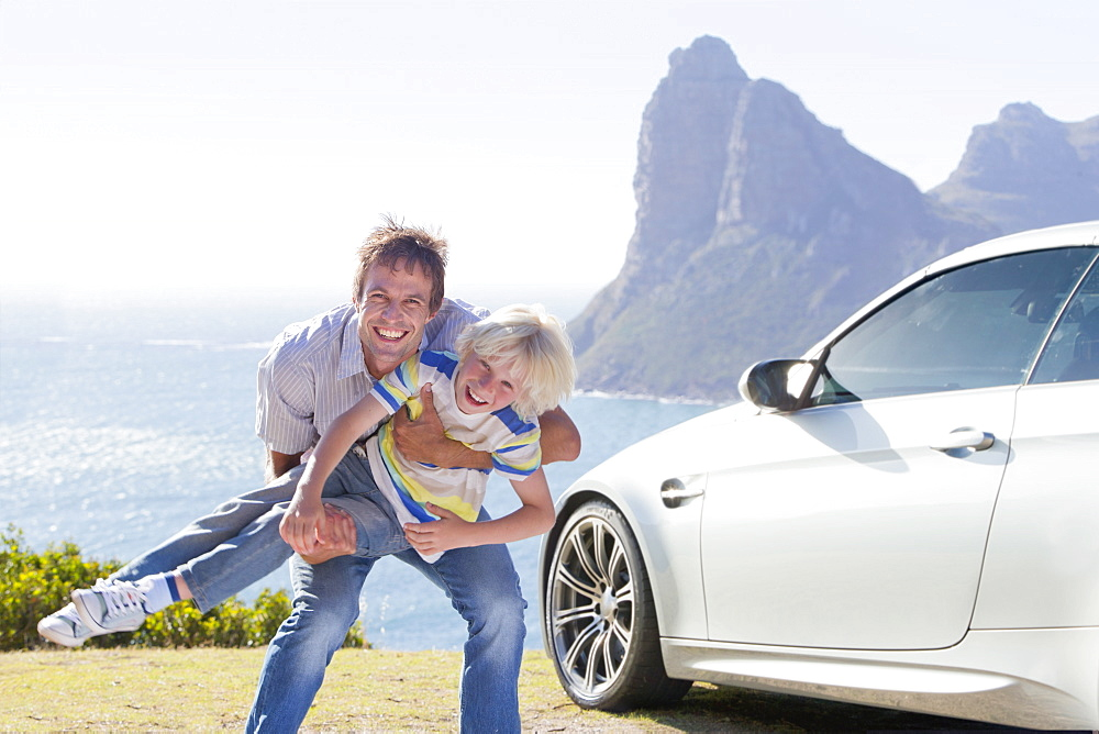 Portrait of enthusiastic father playing with son outside car near ocean