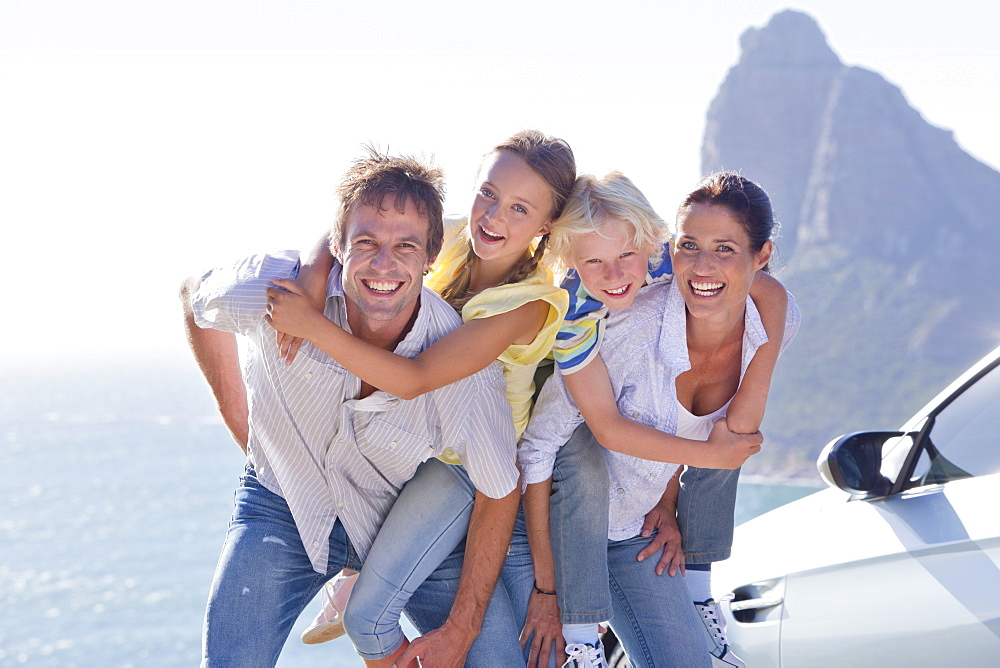 Portrait of enthusiastic family hugging outside car near ocean