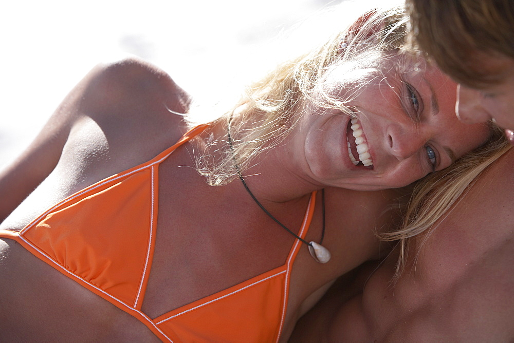 Young couple relaxing on beach, man embracing woman, close-up, woman in orange bikini smiling
